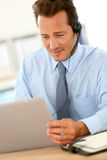Businessman working on laptop with headset Royalty Free Stock Photo