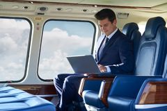 Businessman Working On Laptop In Helicopter Cabin During Flight Royalty Free Stock Photography