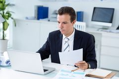 Working on business report. Businessman working on laptop in his office Stock Images