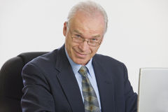 Businessman working on laptop looking at camera. Stock Photos