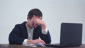 Businessman working on a laptop, lost in the stock market, failure in business. Young businessman working on a laptop, lost in the stock market, failure in stock footage