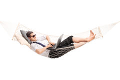 Businessman working on laptop and lying in hammock. Young carefree businessman working on laptop and lying in a hammock  on white background Royalty Free Stock Photos