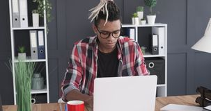 Businessman working on laptop at office. African american businessman working on laptop at office desk stock video footage