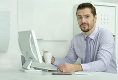 Businessman working with laptop in office. Handsome businessman working with laptop in office Royalty Free Stock Photos