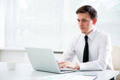 Businessman working at laptop in office. Royalty Free Stock Photo