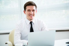 Businessman working at laptop in office. Royalty Free Stock Images