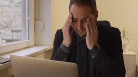 Businessman working on laptop in office headache