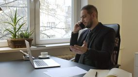Businessman working on laptop in office making phone call nervous and angry. By window black table with notebook papers phone executive corporate stock video footage