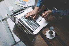 Businessman working with laptop at office.Modern notebook, cup of black coffee and smartphone on the wooden table. Horizontal, blurred, top view Stock Photos