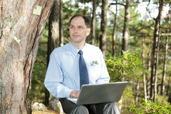 Businessman working with laptop outdoors Royalty Free Stock Images