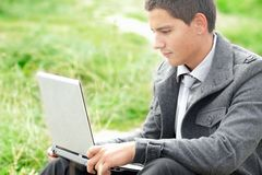 Businessman working on laptop outdoors Stock Images