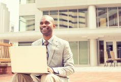 Businessman working on laptop outdoors. Handsome young happy businessman working on laptop outdoors on a background of corporate building. Instagram filter Stock Photography