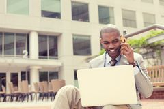 Businessman working with laptop outdoors talking on mobile phone Stock Photo