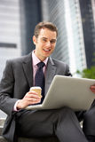 Businessman Working On Laptop Outside Office Royalty Free Stock Images