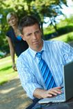 Businessman working with laptop in park Stock Photos