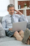 Businessman working on laptop relaxed on the couch Stock Images