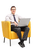 Businessman working on laptop seated in an armchair Royalty Free Stock Image