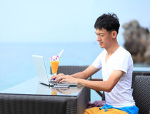 Businessman working with laptop sitting at the beach outdoor. Stock Image