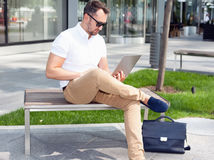 Businessman working on laptop. Sitting on bench Stock Image