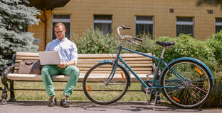 Businessman working on laptop sitting on a bench, next to a bicycle. Handsome man in casual clothes working outdoors Royalty Free Stock Image