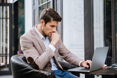Businessman working on a laptop while sitting in cafe Stock Photography
