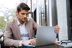 Businessman working on a laptop while sitting in cafe Stock Image