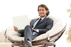 Confident businessman working with laptop sitting in comfortable armchair. Businessman working with laptop sitting in comfortable armchair in living room. photo Stock Photos