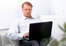 Businessman working on laptop while sitting in a hotel room stock images