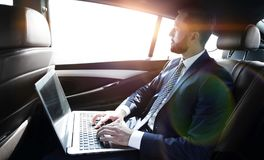 Businessman working with laptop sitting in car Royalty Free Stock Photo