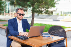 Businessman working on laptop. Sitting at a table on the street in a cafe Royalty Free Stock Photography