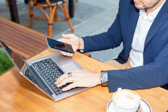 Businessman working on laptop. Sitting at a table on the street in a cafe Stock Photos