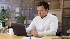 Businessman successfully working on laptop. Businessman working on a laptop in small business office for startup team. Achieving successful deal and raising stock footage
