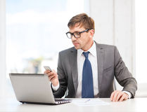 Businessman working with laptop and smartphone. Technology, business and office concept - handsome businessman working with laptop computer and smartphone Royalty Free Stock Images