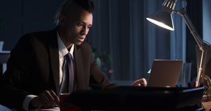 Businessman using laptop and taking notes in night office. Businessman working on laptop and taking notes at late night office stock video footage