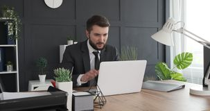Businessman working on laptop and taking notes stock footage