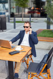 Businessman working on laptop, talking on a cell phone. Businessman working on laptop, sitting at a table on the street in a cafe, talking on a cell phone Stock Images