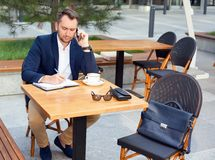 Businessman working on laptop, talking on a cell phone. Businessman working on laptop, sitting at a table on the street in a cafe, talking on a cell phone Royalty Free Stock Images