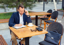 Businessman working on laptop, talking on a cell phone. Businessman working on laptop, sitting at a table on the street in a cafe, talking on a cell phone Stock Photo