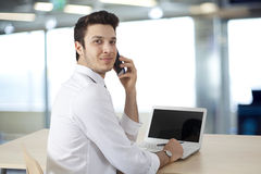 Businessman  working on laptop and talking telephone Royalty Free Stock Images