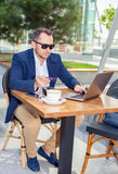Businessman working on laptop, to pay by credit card. Businessman working on laptop, sitting at a table on the street in a cafe, to pay by credit card Royalty Free Stock Images