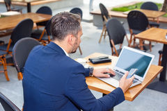 Businessman working on laptop, to pay by credit card. Businessman working on laptop, sitting at a table on the street in a cafe, to pay by credit card Stock Photos