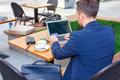 Businessman working on laptop, to pay by credit card. Businessman working on laptop, sitting at a table on the street in a cafe, to pay by credit card Stock Photography
