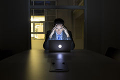 Businessman working late in his office on laptop, night light bu Stock Photo