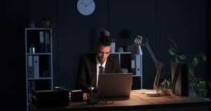 Businessman working late night at office. Young businessman working on laptop late night at office stock footage