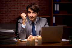 The businessman working late in office with candle light. Businessman working late in office with candle light royalty free stock photo