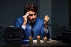 The businessman working late in office with candle light. Businessman working late in office with candle light royalty free stock image