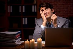 The businessman working late in office with candle light. Businessman working late in office with candle light stock images
