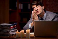 The businessman working late in office with candle light. Businessman working late in office with candle light royalty free stock photos