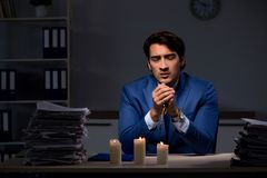 The businessman working late in office with candle light. Businessman working late in office with candle light royalty free stock photography