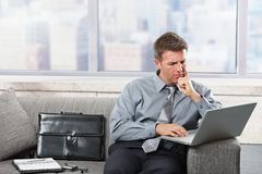 Businessman working on latop on sofa Royalty Free Stock Photography
